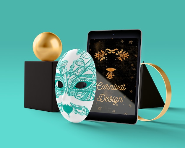 Tablet z motywem karnawałowym obok maski