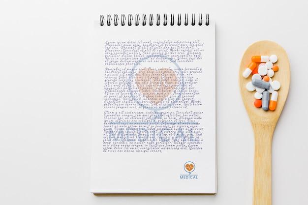Tabletki na drewnianą łyżką z notatnika