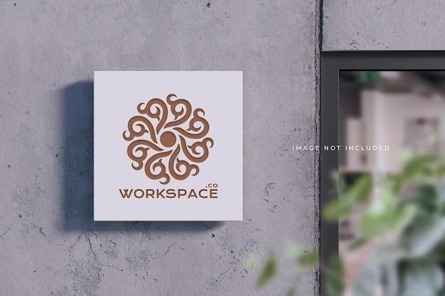Tabliczka z logo na betonowej ścianie - makieta