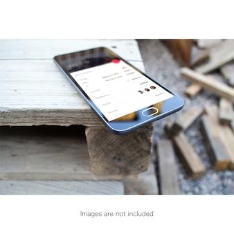 Telefon komórkowy na drewnianym stoliku makijaż