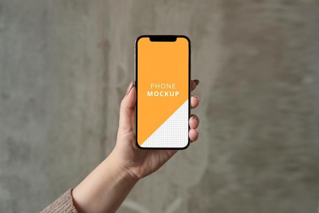 Telefon trzymany w ręku makieta z betonowym minimalistycznym tłem
