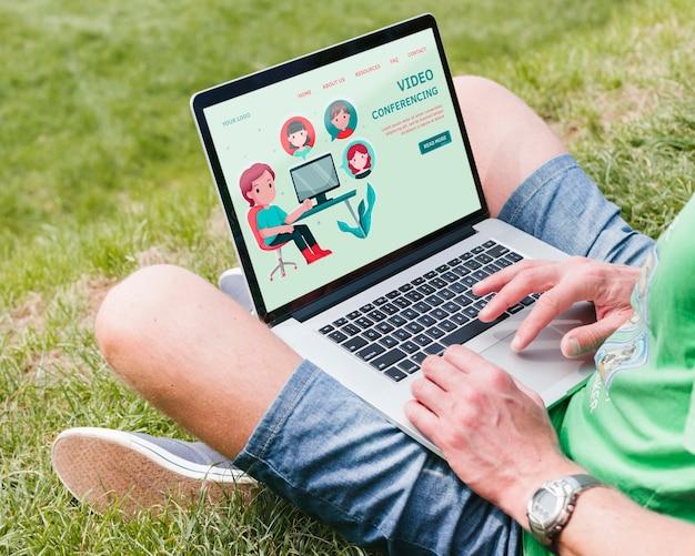 Uczeń pracuje na laptopie na zewnątrz