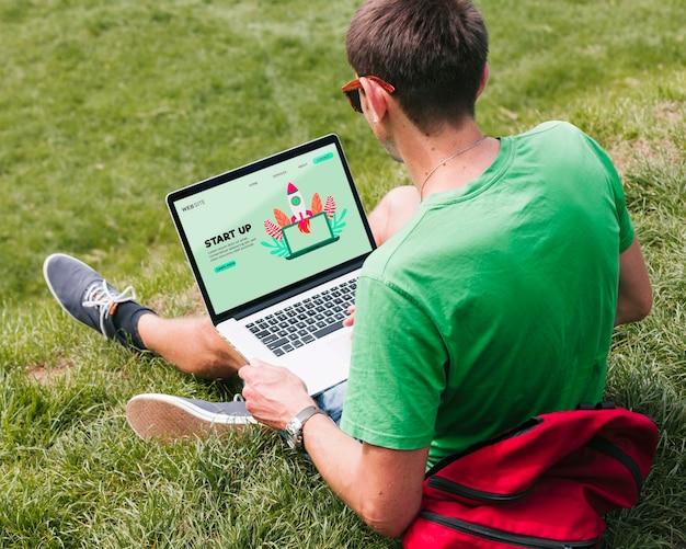 Uczeń pracuje na laptopie outdoors