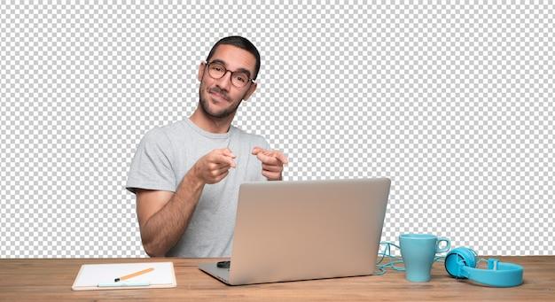 Ufny młodego człowieka obsiadanie przy jego biurkiem i wskazywać z jego ręką
