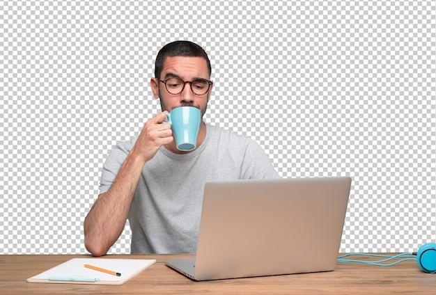 Ufny młodego człowieka obsiadanie przy jego biurkiem pije kawę