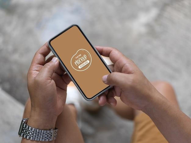 Ujęcie człowieka za pomocą makiety smartfona stojąc na zewnątrz