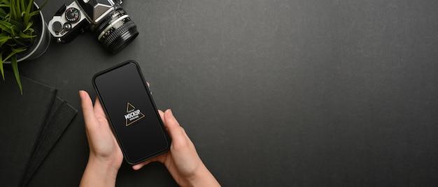 Ujęcie kobiece dłonie przy użyciu makiety smartfona na obszarze roboczym, widok z góry