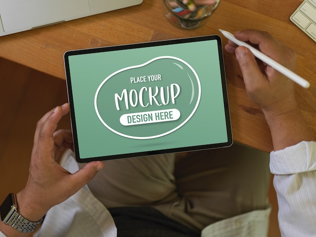 Ujęcie mężczyzny pracownika za pomocą makiety cyfrowego tabletu na drewnianym stole w biurze
