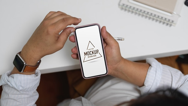 Ujęcie mężczyzny przedsiębiorcy za pomocą makiety smartfona siedząc w miejscu pracy