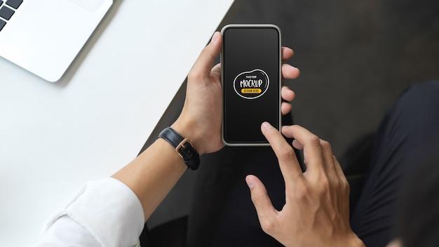 Ujęcie młodego biznesmena za pomocą makiety smartfona, siedząc w swoim biurze