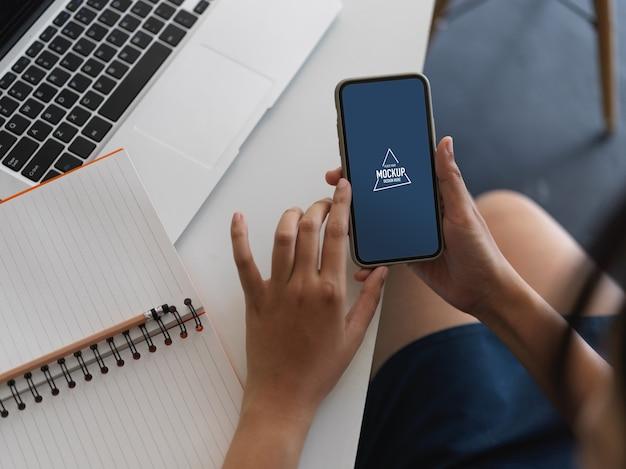 Ujęcie ręki za pomocą makiety smartfona na stole roboczym z laptopa i notebooka