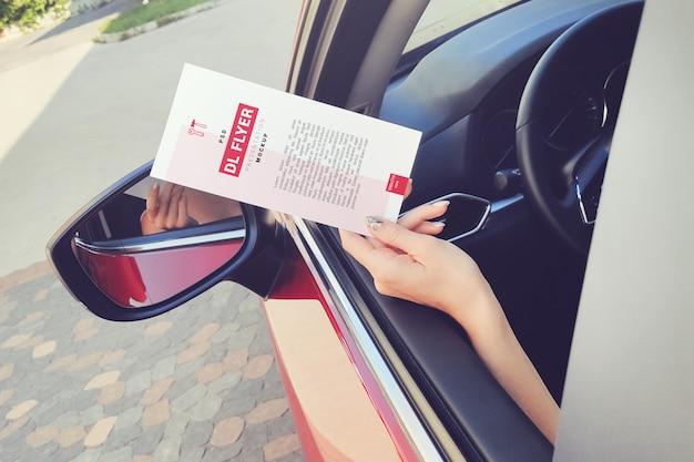 Ulotka dl w dłoni wystaje z makiety okna samochodu