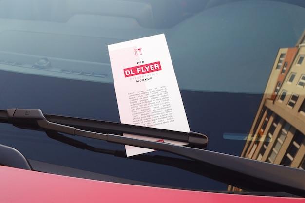 Ulotka reklamowa na przedniej szybie samochodu pod makietą wycieraczek