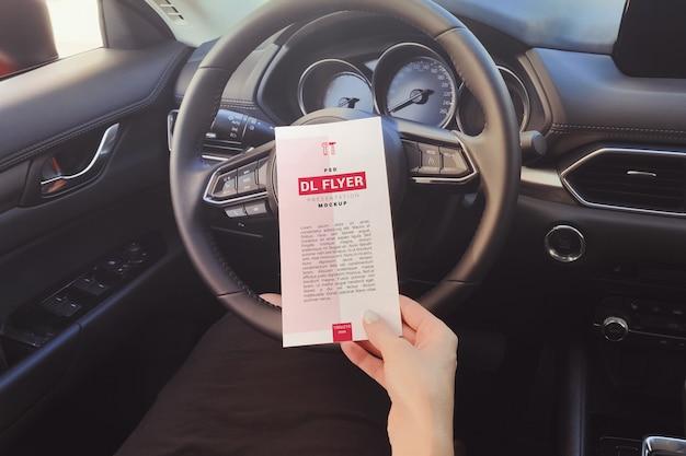 Ulotka w ręce dziewczyny w makieta samochodu