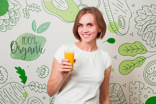 Uśmiechnięta kobieta trzyma sok pomarańczowego