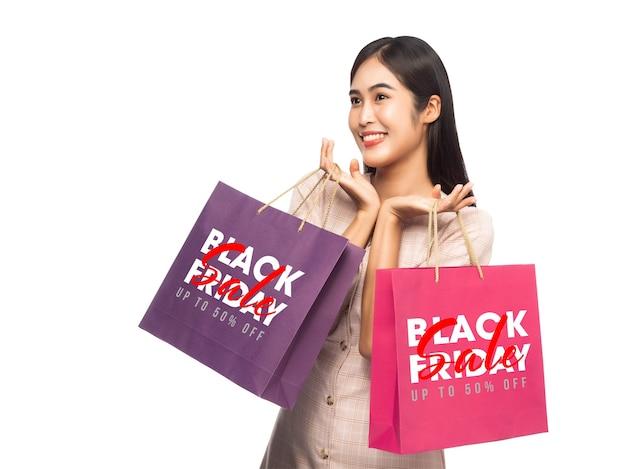 Uśmiechnięta kobieta trzyma torby na zakupy z makietą kampanii czarny piątek