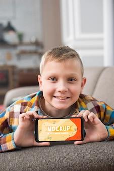 Uśmiechnięty dzieciak na kanapie, trzymając smartfon