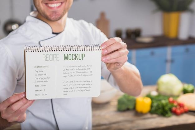Uśmiechnięty kucharz trzyma makietę przepisu