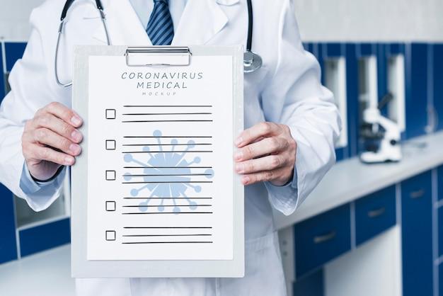 Uśmiechnięty lekarz posiadający makietę papieru medycznego średni strzał