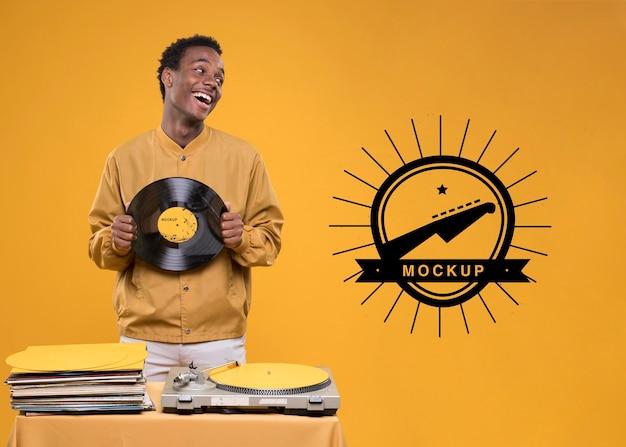 Uśmiechnięty mężczyzna trzyma dysk winylowy do makiety sklepu muzycznego