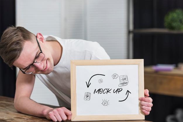 Uśmiechnięty mężczyzna w okularach, trzymając ramkę makiety