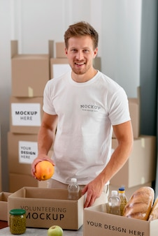 Uśmiechnięty wolontariusz przygotowuje pudełko darowizn z prowiantem
