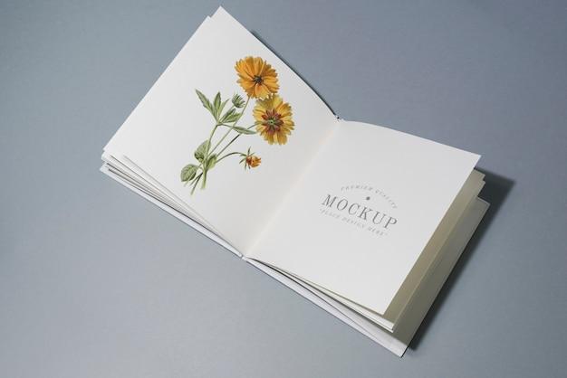 W połowie fałd książki makieta z kwiecistą ilustracją