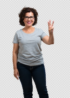 W średnim wieku kobieta pokazuje liczbę trzy z palcami, liczy, pojęcie matematyki, ufny i rozochocony