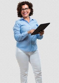 W średnim wieku kobieta uśmiechnięta i ufna, trzyma pastylkę, używa je surfować internet i widzieć ogólnospołeczne sieci, komunikacyjny pojęcie