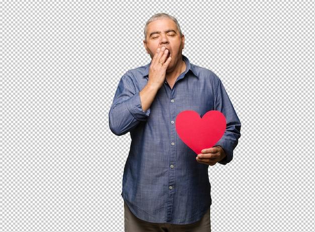 W średnim wieku mężczyzna świętuje valentines dzień zmęczonego i bardzo śpiącego