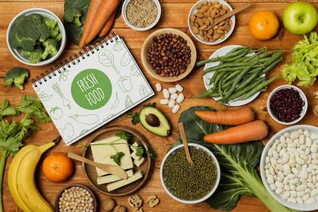 Warzywa leżące na płasko z makietą notesu