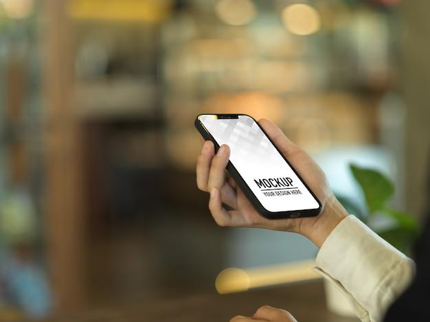 Widok z boku kobiecej ręki trzymającej makietę smartfona