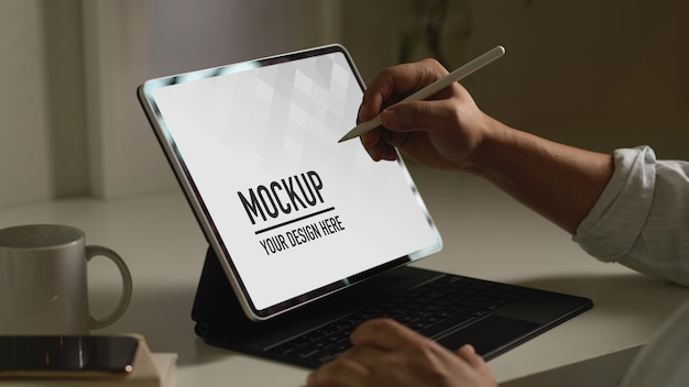 Widok z boku męskiej dłoni za pomocą cyfrowego tabletu z makietą pióra rysika