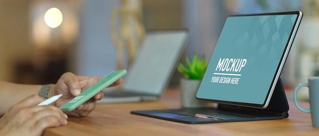 Widok z boku męskiej dłoni za pomocą smartfona podczas pracy z makietą tabletu na drewnianym stole