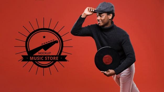 Widok z boku mężczyzny trzymającego dysk winylowy do makiety sklepu muzycznego