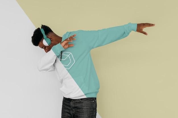 Widok z boku stylowego mężczyzny w bluzie z kapturem ze słuchawkami