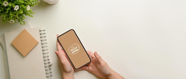 Widok z góry kobiece ręce trzymając makieta smartfona na białym obszarze roboczym