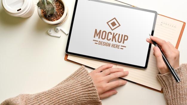Widok z góry kobiety pracującej z makietą cyfrowego tabletu i notatnikiem na białym stole