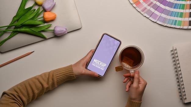 Widok z góry kobiety za pomocą makiety smartfona na obszarze roboczym