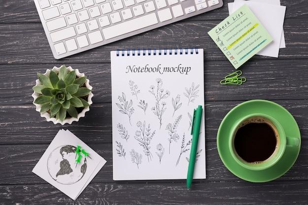 Widok z góry makieta notatnik i artykuły papiernicze w pobliżu kawy i soczystych roślin