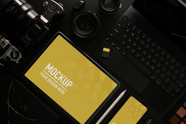 Widok z góry makiety cyfrowego tabletu i smartfona na czarnym stole z aparatem i materiałami cyfrowymi