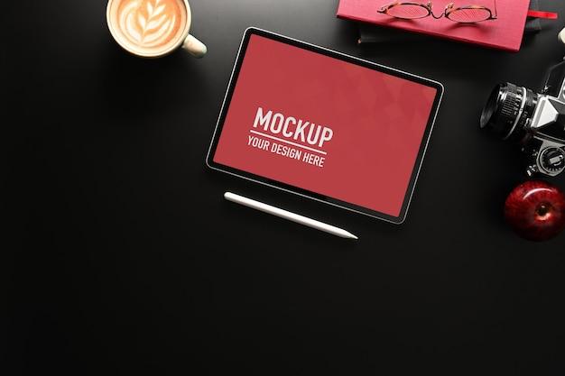 Widok z góry makiety cyfrowego tabletu na czarnym stole z miejscem na kopię, aparatem, notatnikiem i filiżanką kawy