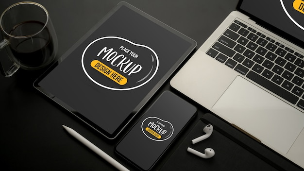 Widok z góry makiety urządzeń cyfrowych z tabletem, smartfonem, laptopem i akcesoriami na czarnym biurku
