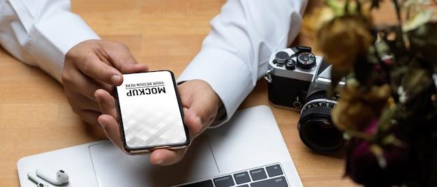 Widok z góry męskich rąk trzymających makietę smartfona na drewnianym stole roboczym