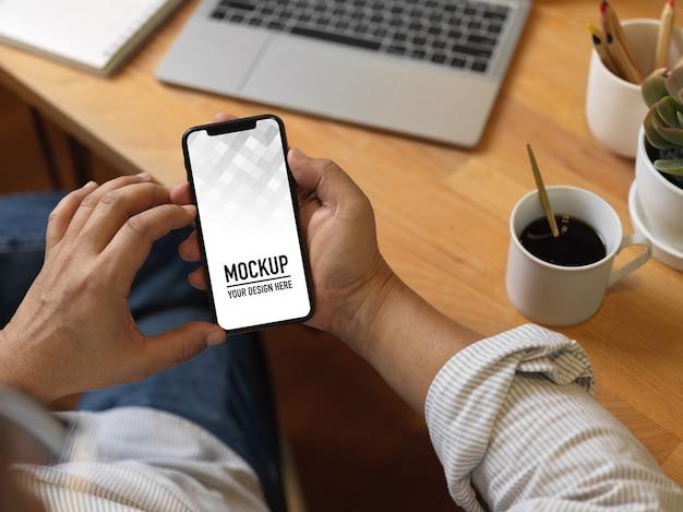 Widok Z Góry Męskich Rąk Za Pomocą Makiety Smartfona Na Drewnianym Stole Roboczym Premium Psd
