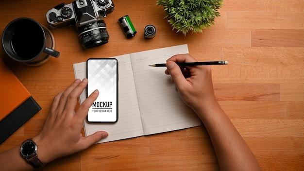 Widok z góry męskiej dłoni pisania na pustym notatniku podczas korzystania z makiety smartfona