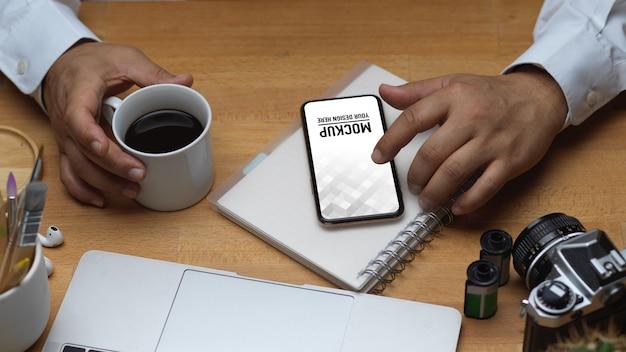 Widok z góry męskiej dłoni za pomocą smartfona i trzymając kubek kawy na obszarze roboczym