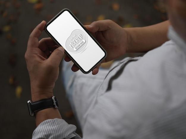 Widok z góry mężczyzny za pomocą makiety smartfona podczas spaceru po ulicy