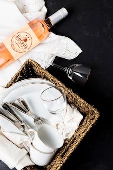 Widok z góry na butelkę wina z koszem i kieliszkami na piknik