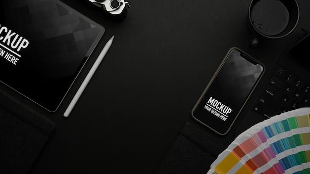 Widok z góry na czarny stół z makietą tabletu i smartfona oraz próbką koloru
